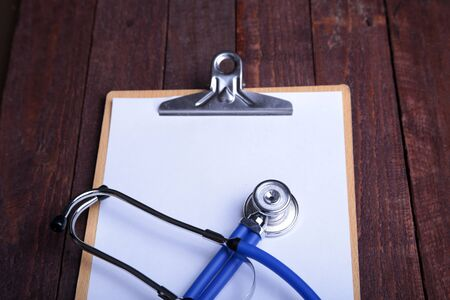Clipboard with blue stethoscope on white background. Health diagnostic concept