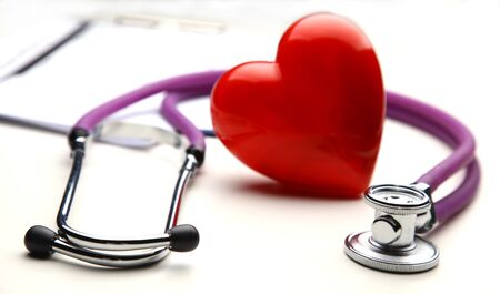 Red heart and a medical stethoscope on desk 版權商用圖片