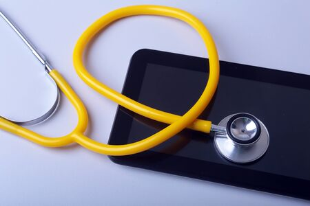 Medical equipment: blue stethoscope and tablet on white background