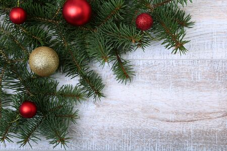 Christmas or New Year background: fur-tree, branches, colored glass balls , decoration and cones on a wooden background