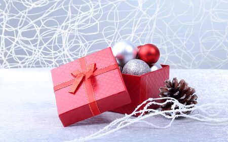 Gift boxes with bow and christmas balls on wood background. Decoration