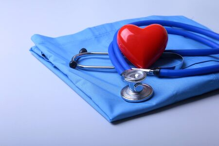 Doctor coat with medical stethoscope and red heart on the desk.