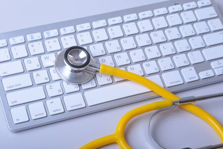A medical stethoscope near a laptop on a wooden table.