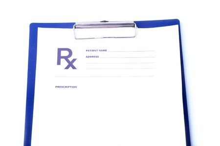 Closeup of medical stethoscope on a rx prescription, red heart isolated on white background.