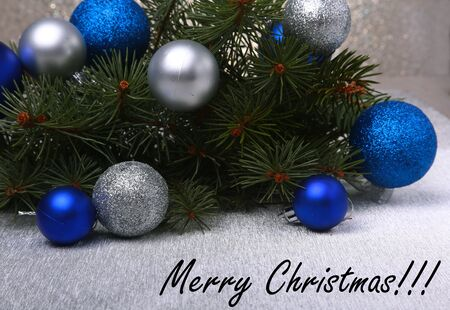 Decorative background with fir branches and red balls on the silver. Christmas card Holiday Concept.