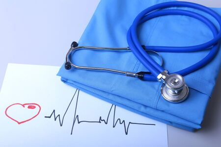 Cardiogram with medical stethoscope and doctor coat on table