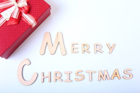 Merry Christmas on white background with gift boxes, fir branches, red decoration. Xmas and New Year card, bokeh, light. Flat lay.