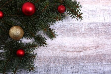 Christmas or New Year background: fur-tree, branches, colored glass balls , decoration and cones on a wooden background.