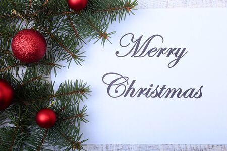 Text merry christmas on paper with fur-tree, branches, colored glass balls , decoration and cones on a wooden background.
