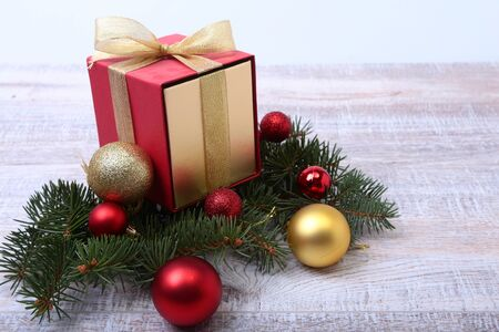 Christmas fir tree with gift box on wooden board.