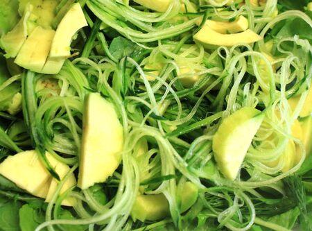 Raw vegan food as background. Salad of greens, fresh vegetables, avocado cucumber arugula, spinach, close-up. 스톡 콘텐츠