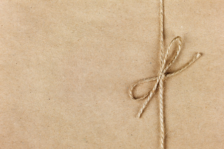 string or twine tied in a bow on kraft paper background 写真素材