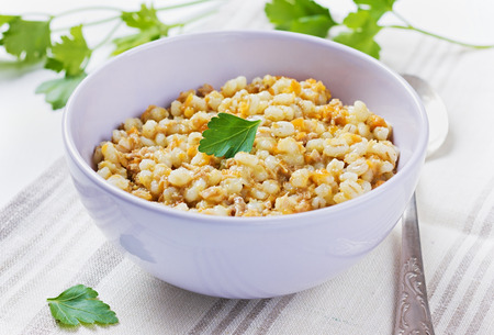 pearl barley: barley porridge in a bowl with meat, vegetables and green parsley, selective focus Stock Photo