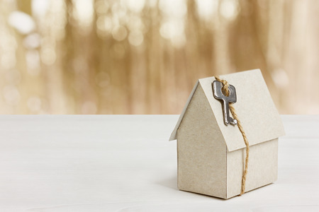 model of cardboard house with key against bokeh background. house building, loan, real estate or buying a new home concept. Stock Photo