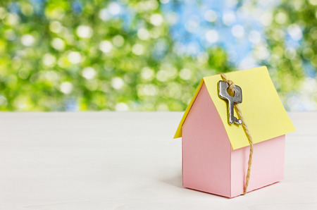 housewarming: model of cardboard house with a bow of twine and key against green bokeh background. house building, loan, real estate or buying a new home concept.