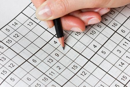 vrouw de hand houden van een potlood en lost kruiswoordraadsel sudoku, populaire puzzelspel met nummers