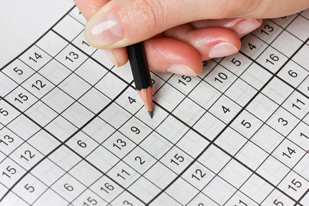 Ordinal: woman hand holding a pencil and solves crossword sudoku, popular puzzle game with numbers Stock Photo