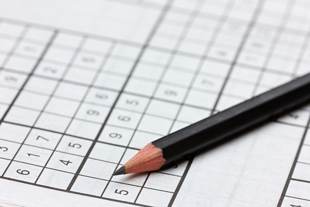 conundrum: crossword sudoku and pencil, popular puzzle game with numbers Stock Photo