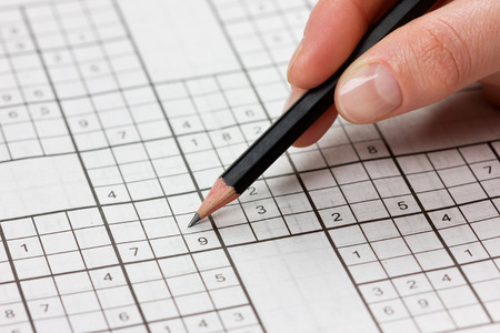 solves: woman hand holding a pencil and solves crossword sudoku, popular puzzle game with numbers Stock Photo