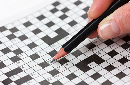 solves: woman hand holding a pencil and solves crossword puzzle Stock Photo