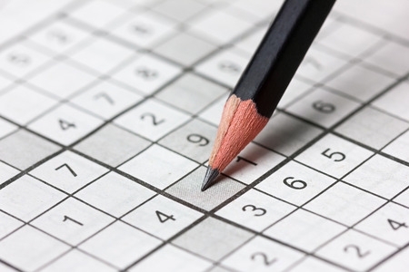 Ordinal: crossword sudoku and pencil, popular puzzle game with numbers Stock Photo