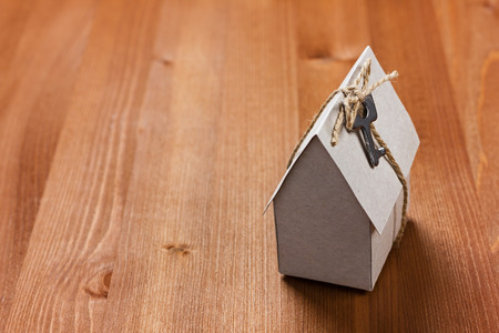 housewarming: model of cardboard house with a bow of twine and key. house building, loan, real estate or buying a new home concept. Stock Photo