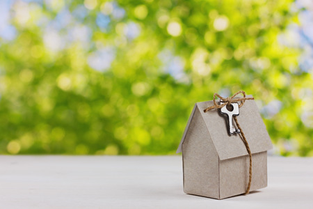 real estate background: model of cardboard house with a bow of twine and key against green bokeh background. house building, loan, real estate or buying a new home concept.