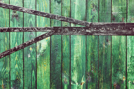 wicket gate: old wooden planks with green color paint and black metal plate, wood gate background Stock Photo