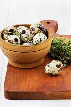 speckle: Quail eggs with a thyme in a wooden cup on a brown kitchen board on a white surface