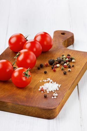 salt pepper: Cherry tomatoes with color pepper and sea salt on a brown kitchen board on a white wooden surface