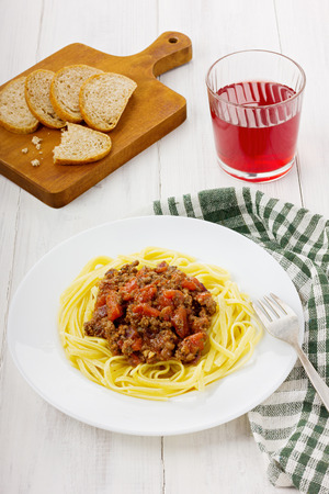 mincemeat: Pasta with sauce a bolognese from tomatoes and mincemeat on a white plate