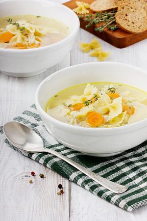 sopa de pollo: Sopa de pollo en un plato blanco con una cuchara sobre una mesa de madera blanca