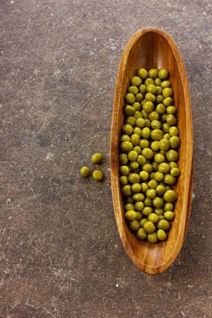 green peas: Canned green peas in wooden bowl Stock Photo