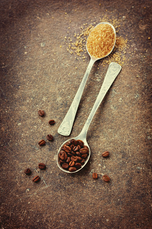 brown sugar: Coffee beans and brown sugar in a spoon on a vintage surface