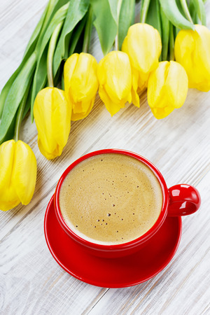 Cup of coffee and spring yellow tulips on white wooden background, elegantly served breakfast photo