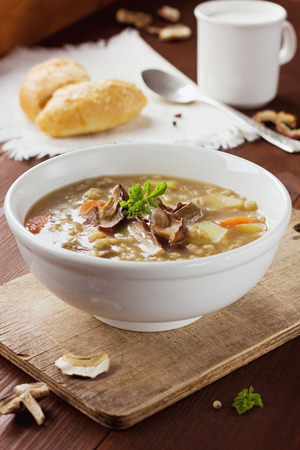 pearl barley: Homemade vegetarian mushroom soup with barley and vegetables in white plate on a vintage wooden board