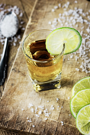 Tequila shot with lime and salt on vintage wooden background photo