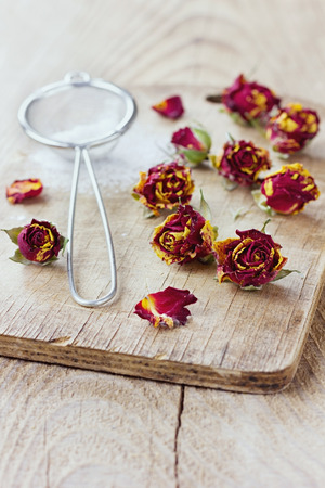 icing sugar: Dried rose buds and aromatic icing sugar on wooden rustic table, selective focus