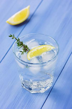 water thyme: El agua con lim�n y hielo decorado tomillo sobre una mesa de madera azul