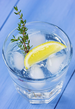 water thyme: Water with lemons and ice decorated herb thyme on a blue wooden table Stock Photo