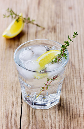 water thyme: Water with lemons and ice decorated herb thyme on a rustic wooden table Stock Photo