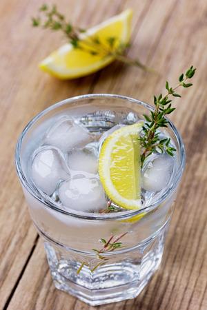 water thyme: El agua con lim�n y hielo decorado tomillo sobre una mesa de madera r�stica