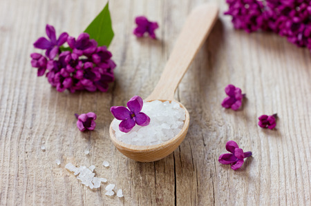 Spa composition with sea salt bath in wooden spoon and lilac flowers on a rustic surface, aromatherapy photo