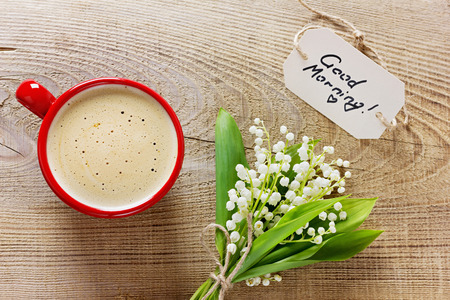 Coffee cup with flowers and notes with words of love on a wooden rustic background