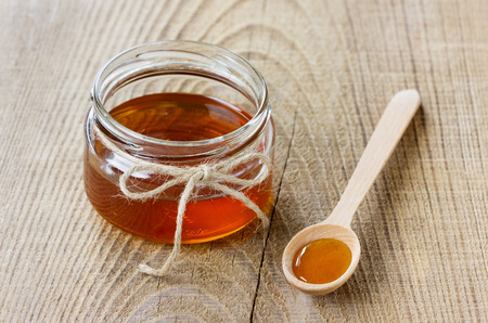 honey pot: Honey in a wooden spoon and jar on a wood rustic background