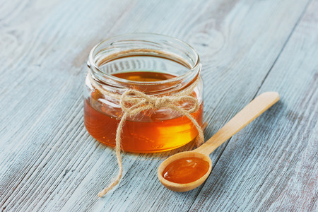 Honey in a wooden spoon and jar on a blue background