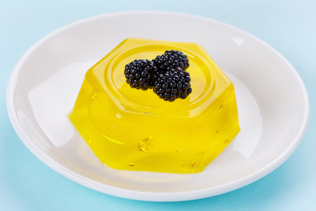dietetical: pineapple jelly pudding decorated blackberries on a white plate on a blue background