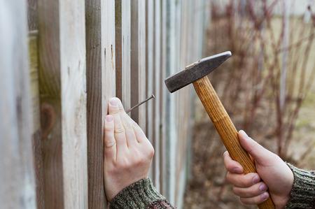 las manos del hombre en coche clavo con un martillo en la cerca de madera, carpintería