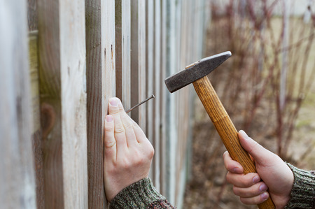 man hands drive nail with a hammer in wooden fence, carpentry Archivio Fotografico
