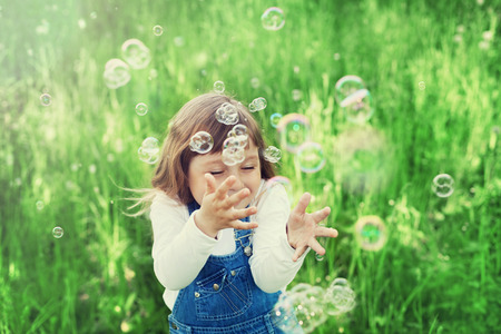 cute little girl playing with soap bubbles on the green lawn outdoor, happy childhood concept, child having fun, vintage toned photo